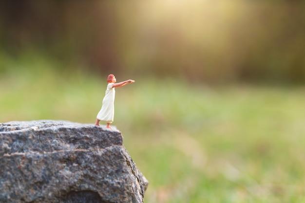 Gente en miniatura: mujer soñolienta que sufre de sonambulismo en un acantilado de roca con fondo de naturaleza
