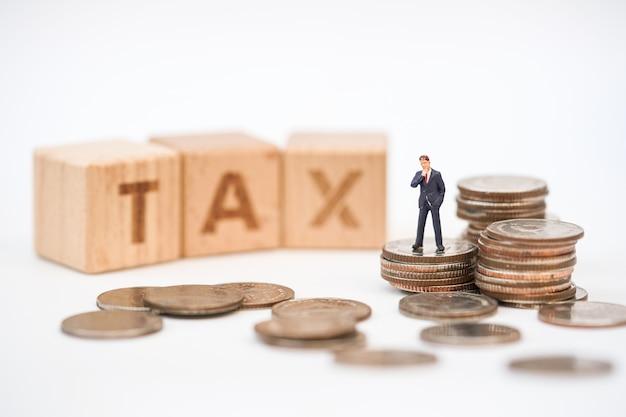 Gente en miniatura, oficial de impuestos con el bloque de palabras