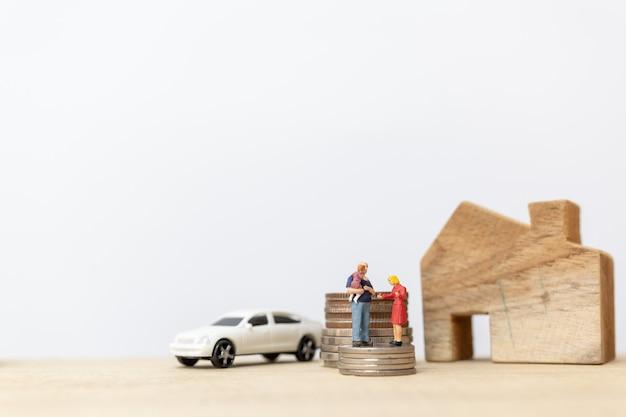 Gente en miniatura: padres con hijos con apilamiento de monedas y casa