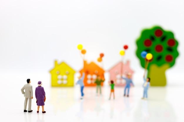Gente en miniatura: los padres que buscan niños juegan y sostienen globos con casas.