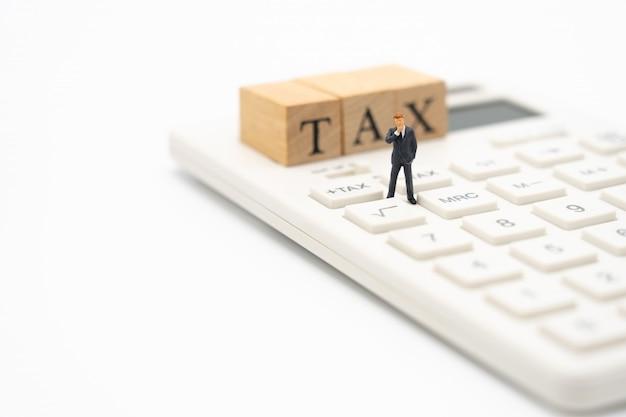 Gente en miniatura pagar en la cola ingreso anual (impuestos) para el año en la calculadora.