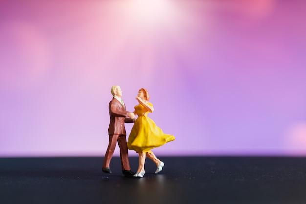 Gente en miniatura, pareja bailando con colores de fondo.