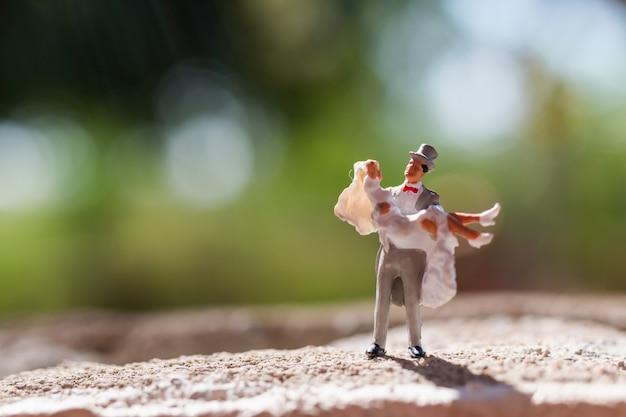 Gente en miniatura: pareja de pie en el parque
