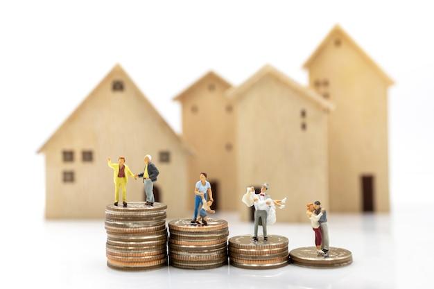 Gente en miniatura: persona mayor de pie sobre la pila de monedas con el hogar, el concepto de planificación de la jubilación.