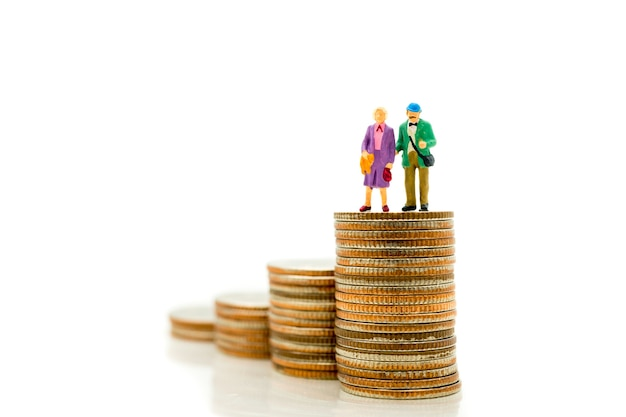 Gente miniatura, personas de edad avanzada que se colocan en monedas de la pila usando como retiro del trabajo