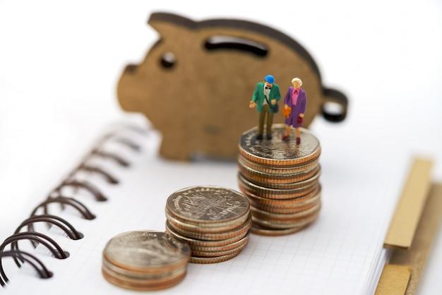 Gente en miniatura: personas mayores felices de pie en la pila de monedas, concepto de jubilación.