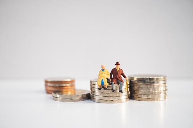Gente en miniatura, personas mayores sentadas en monedas de pila que usan como concepto de jubilación laboral