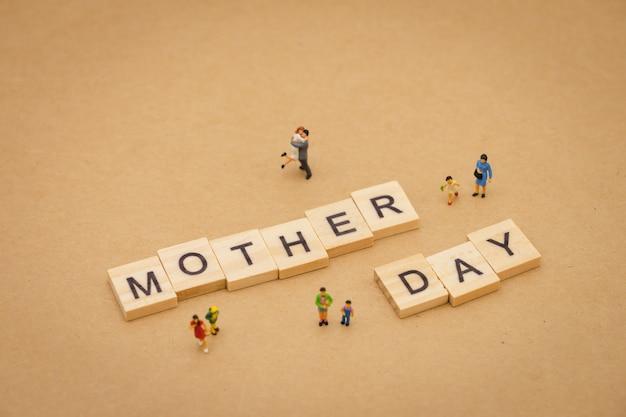 Gente en miniatura de pie con la palabra de madera día de la madre usando como fondo día universal
