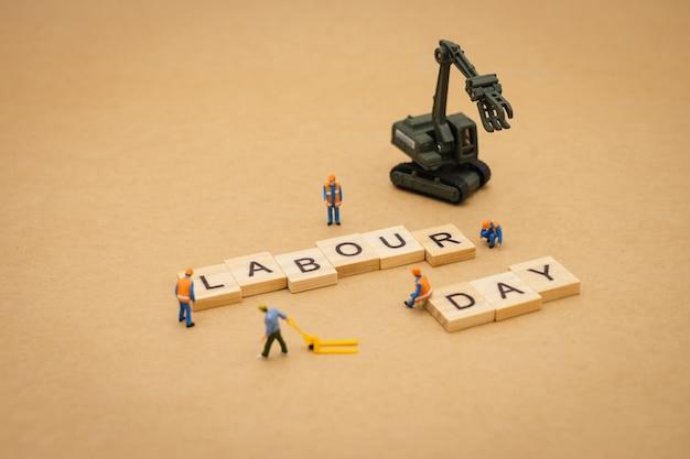Gente en miniatura de pie con la palabra de madera día del trabajo usando como fondo día universal