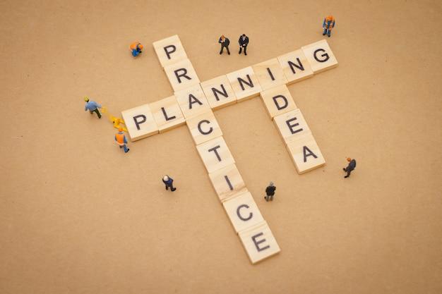 Gente en miniatura de pie con la palabra de madera planificación, práctica e idea
