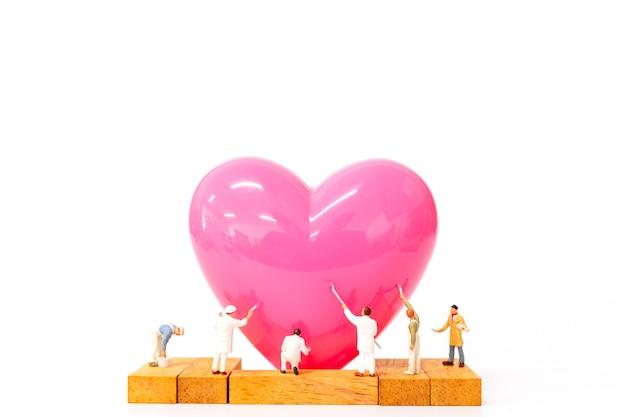 Gente miniatura pintando corazón rosa sobre fondo blanco