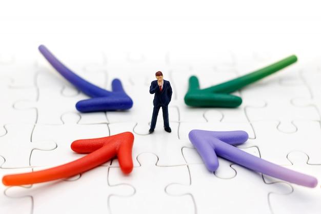 Gente miniatura que se coloca con la opción del camino de la flecha. concepto de decisión empresarial.