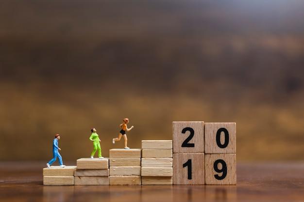 Gente miniatura que se ejecuta en el bloque de madera número 2019