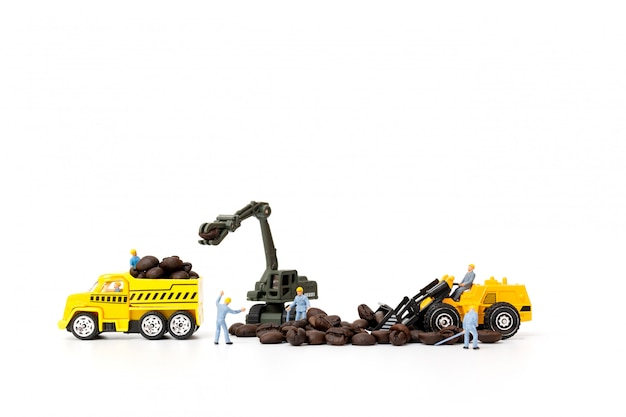 Gente en miniatura que trabaja con granos de café tostado