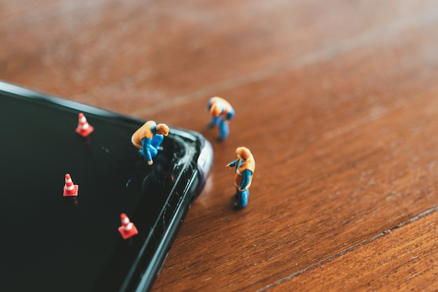 Gente en miniatura reparación trabajador de la construcción teléfono inteligente