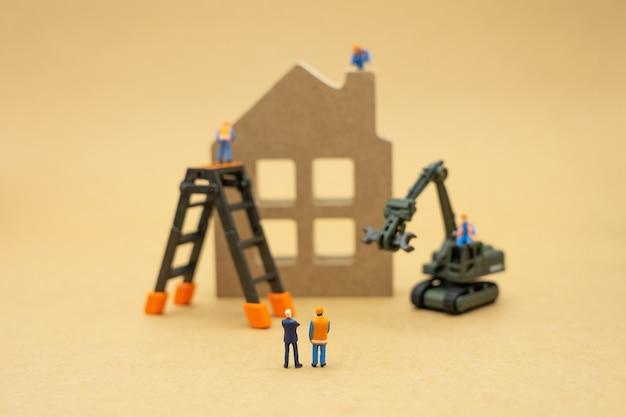 Gente en miniatura reparación de trabajadores de construcción un modelo de casa modelo