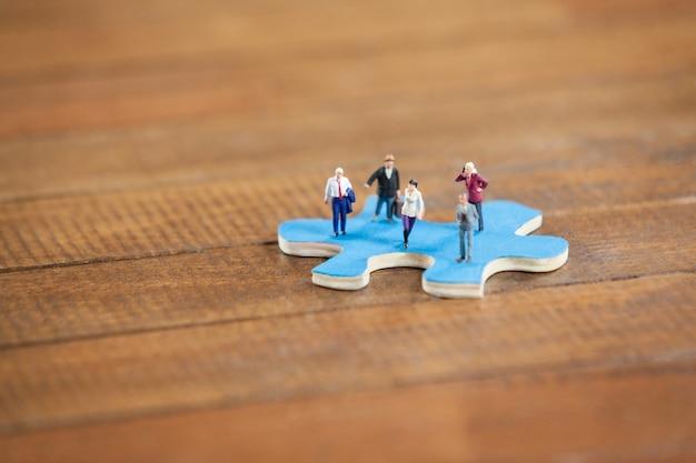 La gente miniatura en un rompecabezas