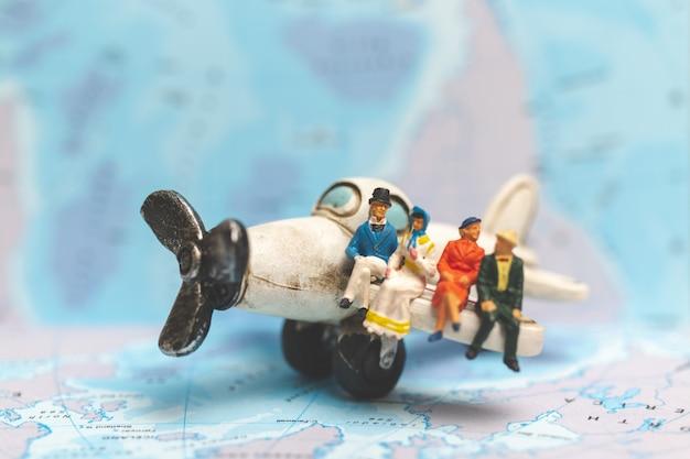 Gente en miniatura sentada en el avión con fondo de mapa mundial