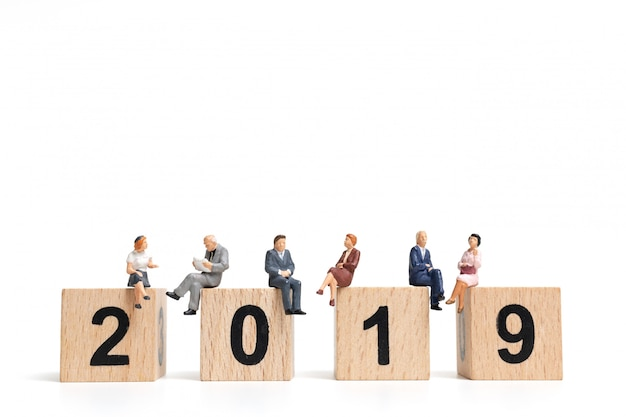 Gente miniatura sentada en el bloque de madera número 2019