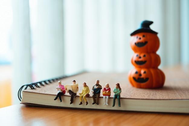 Gente miniatura sentada en el libro con fondo de calabaza fantasma