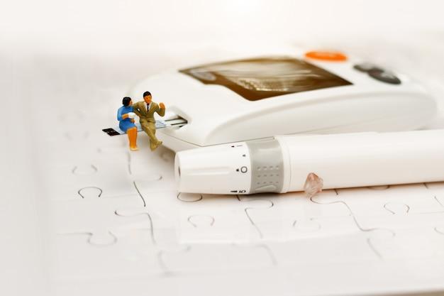 Gente miniatura sentada en un medidor de glucosa de diabetes, concepto de atención médica.