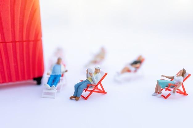 Gente en miniatura sentado en los asientos de playa para tomar el sol y equipaje. concepto de verano