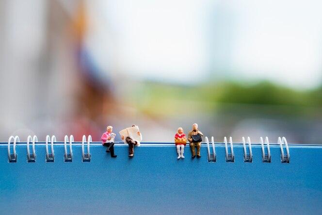 Gente miniatura sentado en papel usando como concepto de educación y fondo social