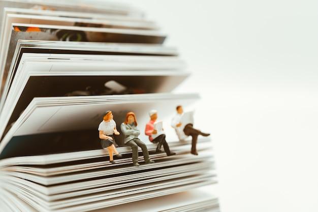 Gente miniatura sentado en papel usando como educación y social