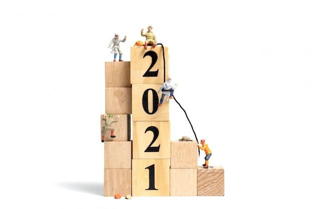 Gente en miniatura: sube en un cubo de madera con el número 2021