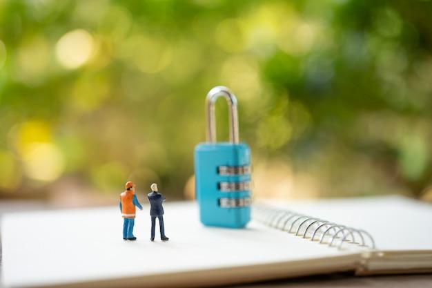 Gente en miniatura trabajador de la construcción reparación de llaves de seguridad y el tratamiento