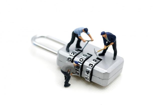 Gente en miniatura: trabajador hackeando en candado de seguridad.