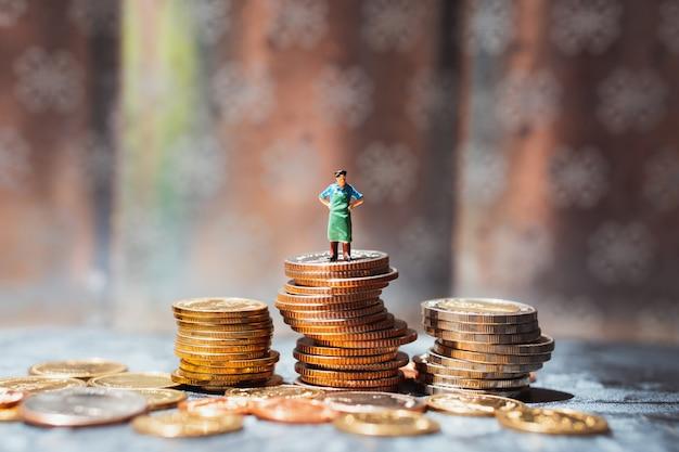 Gente en miniatura, trabajador parado sobre pila de monedas