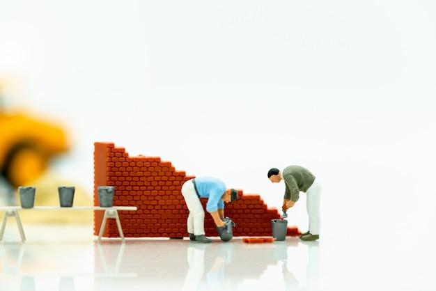 Gente en miniatura: los trabajadores arreglan la pared antes que el mundo. conceptos de resolución de problemas.