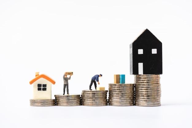 Gente en miniatura, trabajadores moviendo cosas a una nueva casa en pilas de monedas.