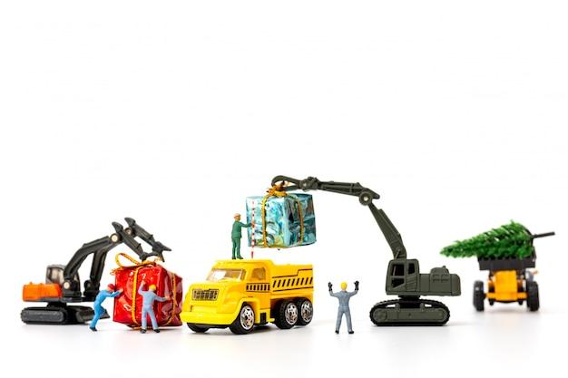 Gente miniatura trabajando en una caja de regalo