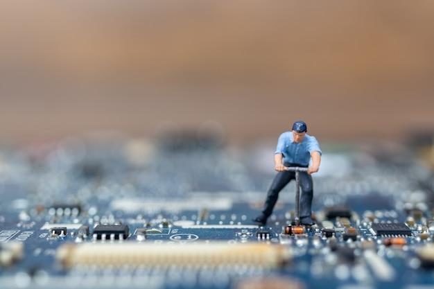 Gente en miniatura trabajando en placa cpu