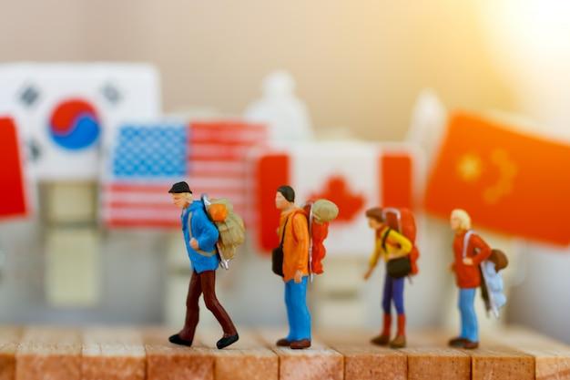 Gente en miniatura: viajero con mochila caminando caja de madera.