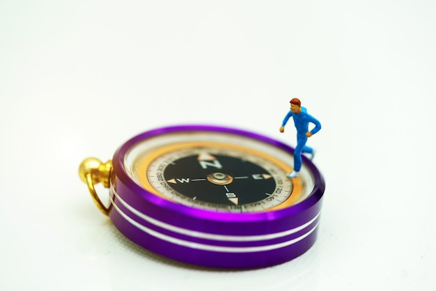Gente en miniatura: viajero de pie en la brújula.