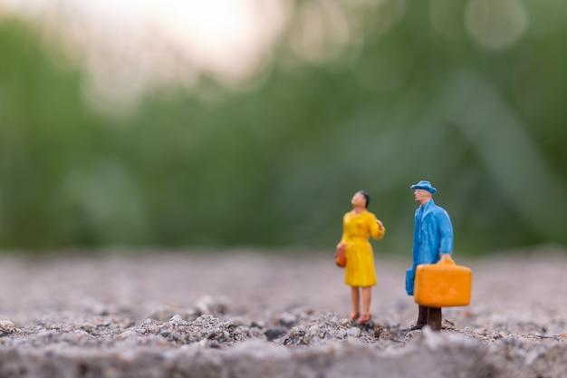 Gente en miniatura, viajero sosteniendo un bolso de pie en el parque