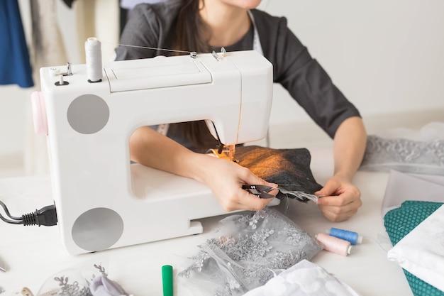 Gente, modista, sastre y concepto de moda - cerca del joven diseñador de moda en su sala de exposición