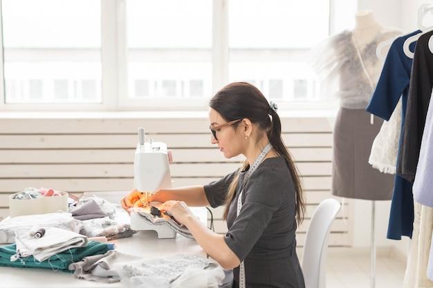 Gente, modista, sastre y concepto de moda - joven diseñadora de moda en su sala de exposición