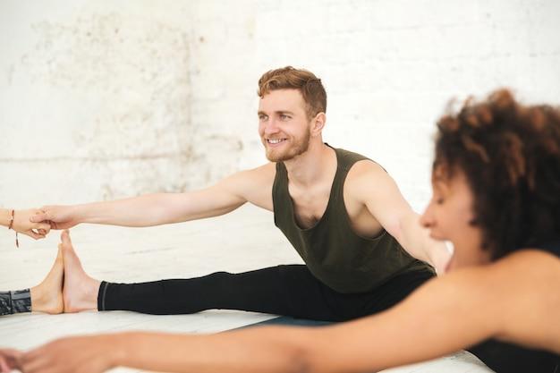 Gente multiétnica feliz en estiramiento de estudio de yoga.