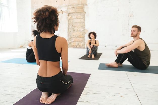 Gente multiétnica feliz en estudio de yoga