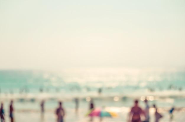 Gente de multitud borrosa en la playa en verano