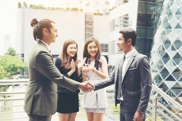 Gente de negocios agitando las manos, terminando un acuerdo de éxito de la reunión.