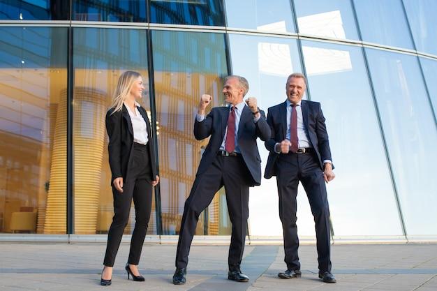 Gente de negocios alegre celebrando la victoria, de pie juntos en la fachada del edificio de oficinas de cristal. vista frontal de cuerpo entero. equipo exitoso y concepto de trabajo en equipo