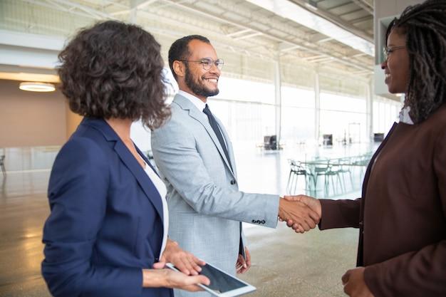 Gente de negocios alegre estrechándole la mano