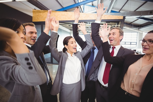 Gente de negocios alegre levantando las manos