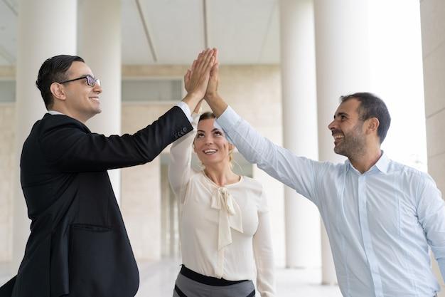 Gente de negocios alegre que da cinco altos para celebrar el éxito