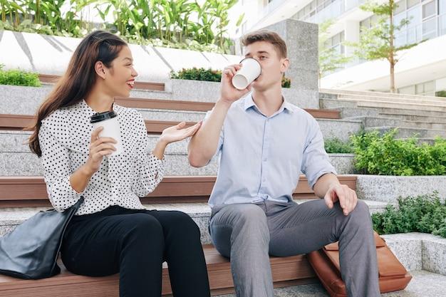 Gente de negocios alegre sentada en un banco, bebiendo café para llevar y discutiendo noticias durante el descanso